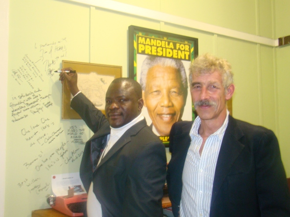 Signing the wall at Ikes Books. Dr Segun Ige and Prof Tim Quinlan